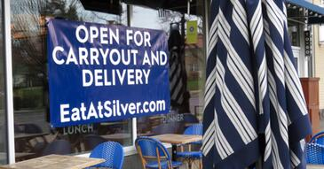 Picture of restaurants showing with sign showing that they are open for business with carryout and delivery.