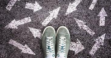 Arrows on sidewalk in chalk with feet in sneakers stock photo
