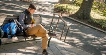 Student sitting on a bench outside Kogod