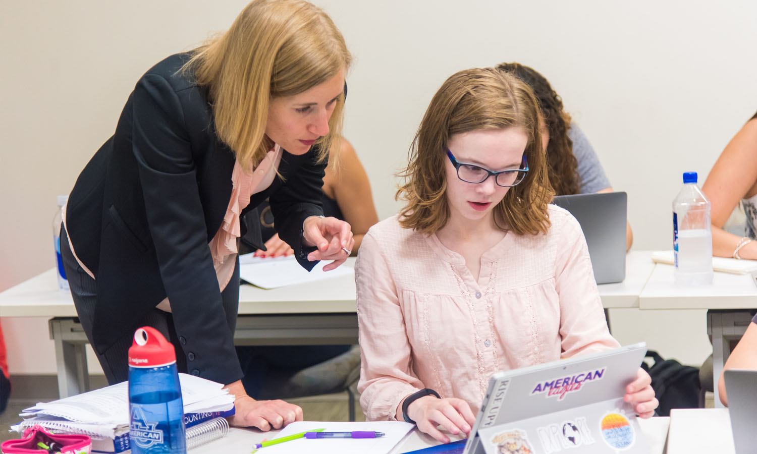 Professor helping student in accounting class