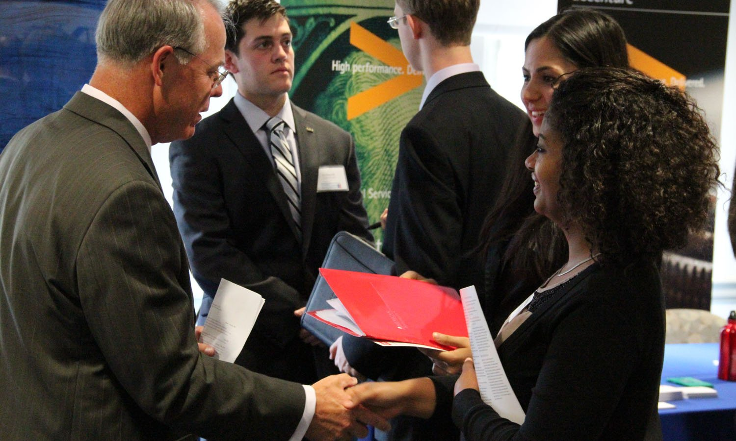 Student shaking hands with a recruiter at a job fair