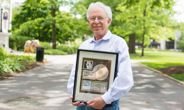 Professor John Simson holding a Platinum sales award